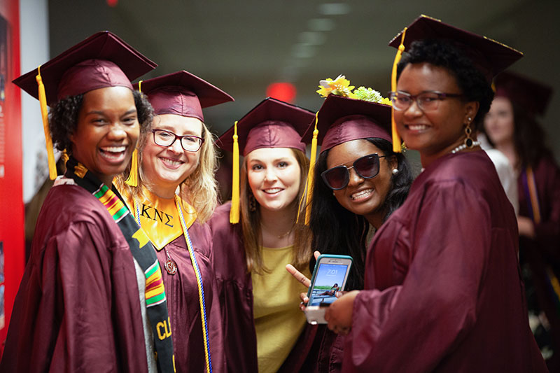 Five Students at Commencement dressed in regalia