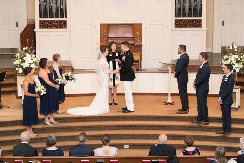 Bride and Groom standing at alter with Bridesmaids and Groomsmen