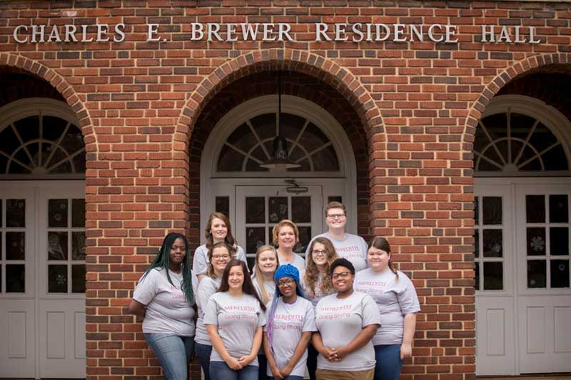 Ten students and one teacher taking a group photo in front of Brewer Residence Hall