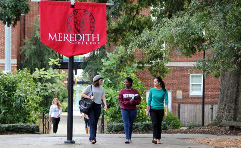 Three students walk together on Meredith's campus. A Meredith College banner, the words Meredith College in white on a maroon background, is in the foreground of the photo.
