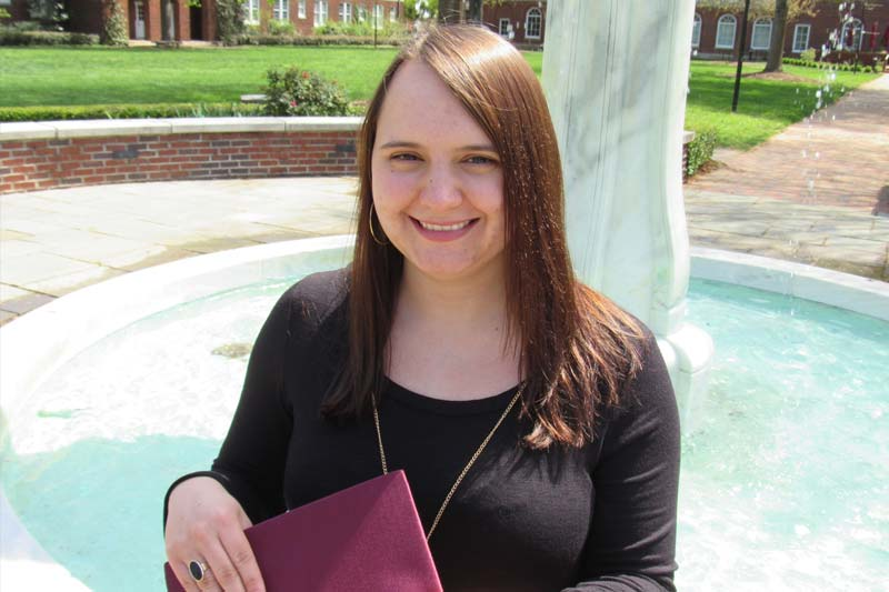 Profile photo of Rachael Martin standing on campus with her graduation cap in her hand