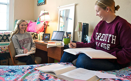 Two women students wearing Meredith shirts sit together in their residence hall room.