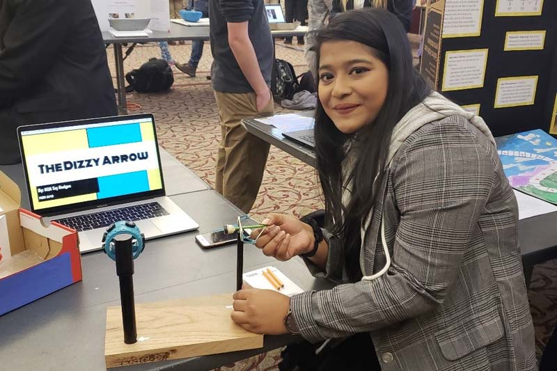 Abiha Khanam sitting in front of her toy design, The Dizzy Arrow.
