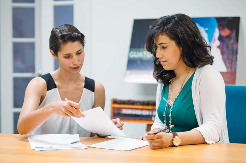 Two women looking at paperwork at a desk.