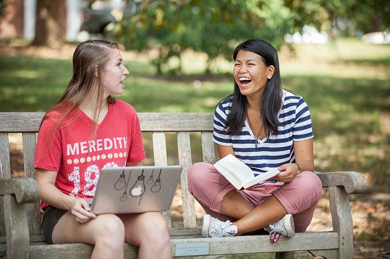 Two Meredith College students talking outside a residence hall