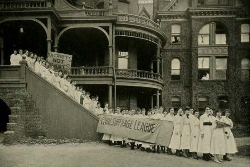 Women lining a stairwell outside of Old Meredith Campus holding banner with words Equal Suffrage League Sign