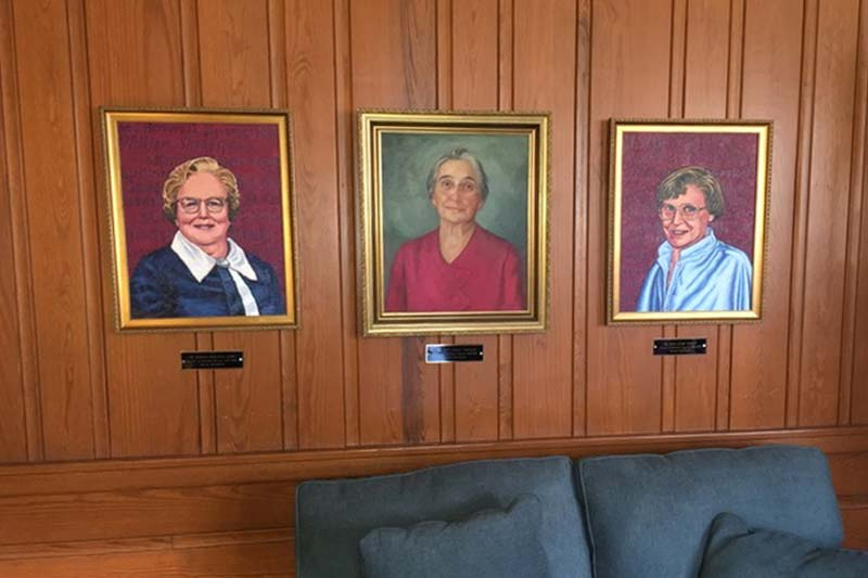 Three portraits hanging on a wood panel wall in Joyner Lounge