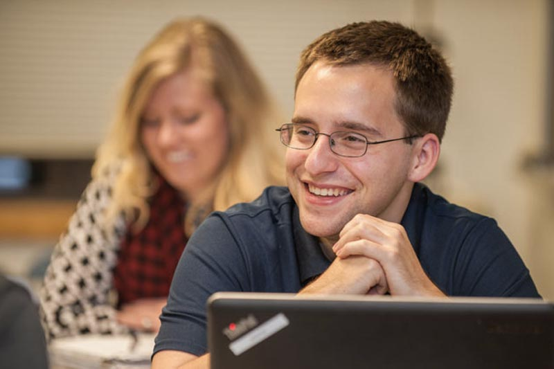 Male Paralegal smiling in classroom with female student visible in background