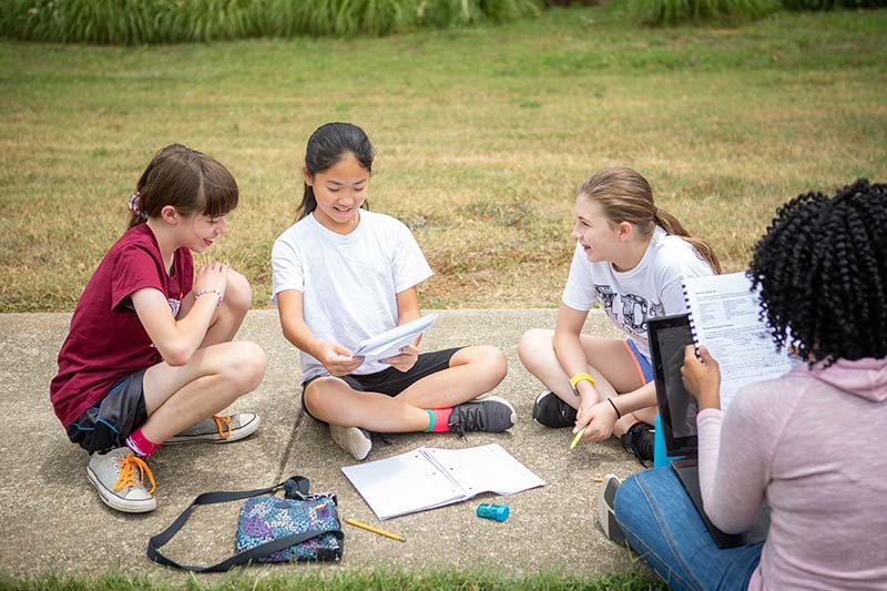 Young Writers Camp - Students on sidewalk discussing literature