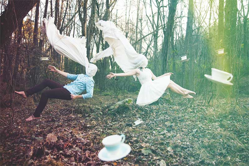 Dream like photo of people suspended in air in a forest