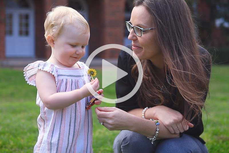 Mother looking at child holding yellow flower