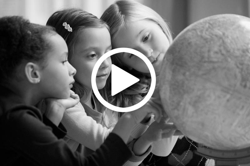 click on image of girls looking at Globe to watch a video about the Status of Girls