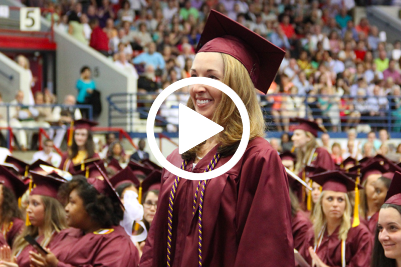Click on image of female graduate at commencement to watch Wings Program Video in Modal