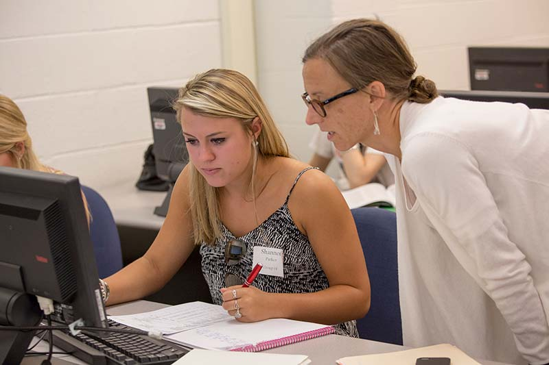 Faculty helping student in Class in computer lab