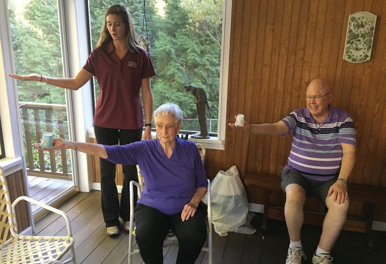 a young female student helping an elderly couple with their balance