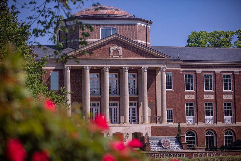Image of Johnson Hall with a rosebush out of focus in left corner foreground.