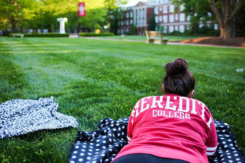 student lying in courtyard grass with dorms visible