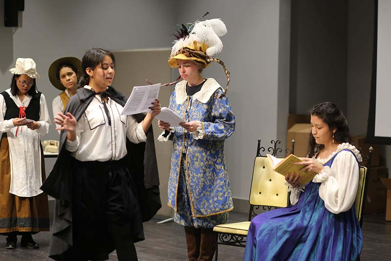 Five students dressed up in costume as they present a Spanish skit