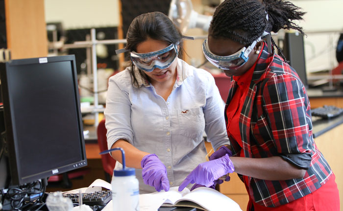 Two Meredith students with goggles and gloves working in a science lab