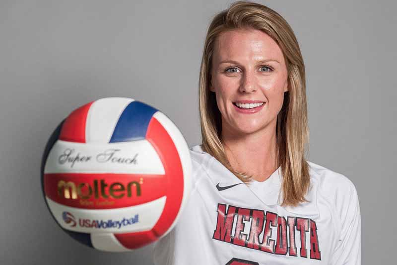 Meredith student-athlete Caroline Corey holding a volleyball