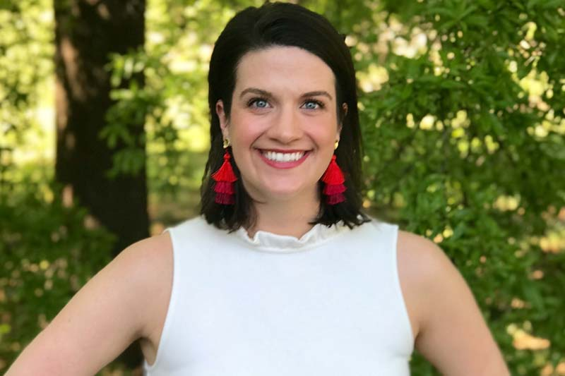 Image of Ellison White wearing white top and red earrings