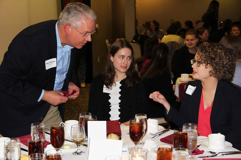 Two Meredith students networking with a working professional during the Networking and Etiquette Dinner