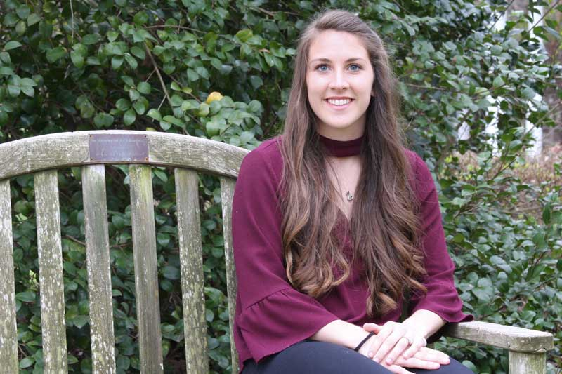 Profile photo of Haley Ervin sitting on a wooden bench on the Meredith campus