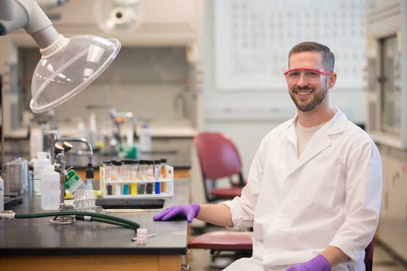 Hunter Peden in a white lab coat sitting in a Biology lab