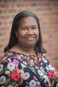 Lori White smiling against brick wall