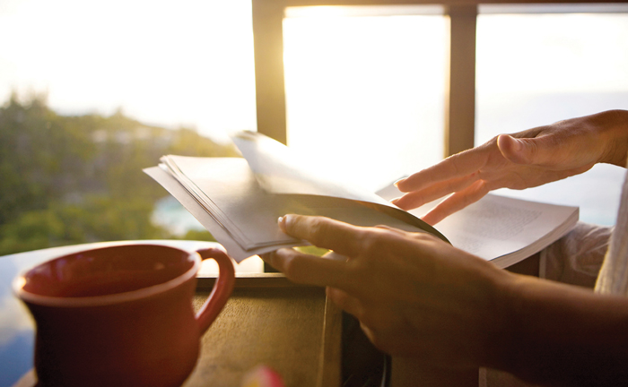 reaching for book with coffee in hand