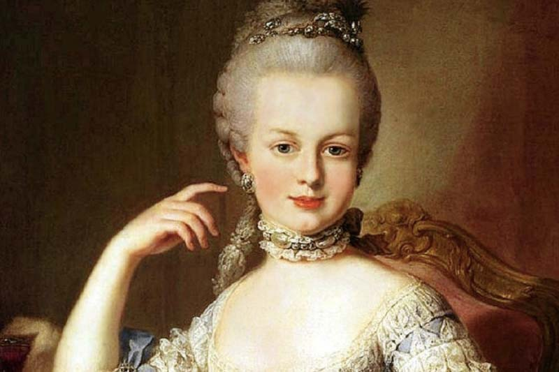 Painting of Marie Antoinette sitting in a chair wearing a white dress