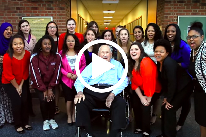 Click on image of Portor Byrum seated in chair with students to watch his donor video in modal