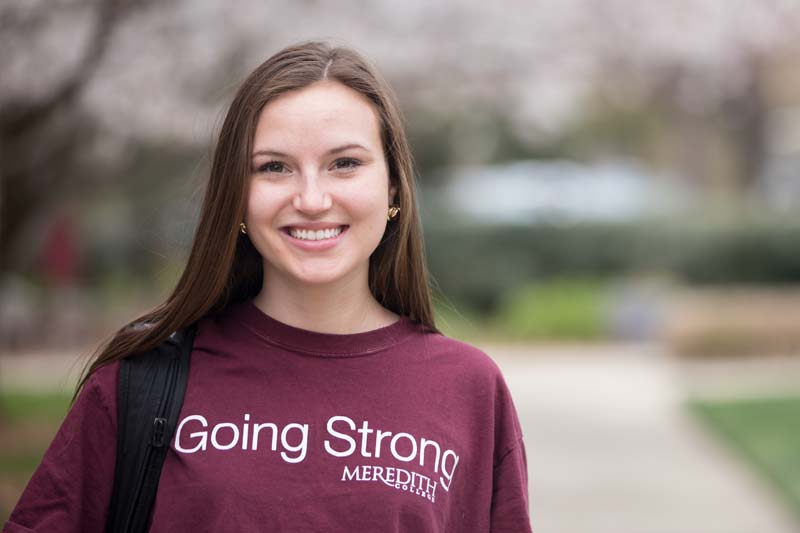 Image of Rachael Nicholos wearing a sweatshirt with the words Going Strong Meredith College