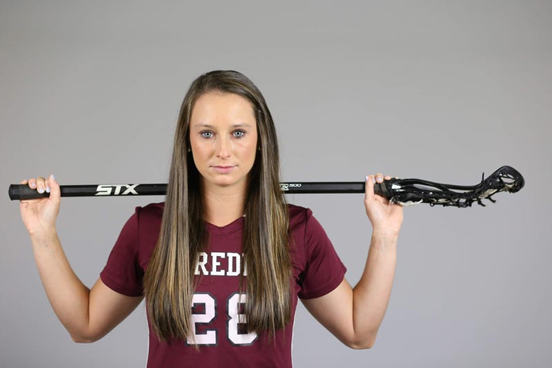 Profile photo of Sarah Arbes holding a lacrosse stick across her shoulders
