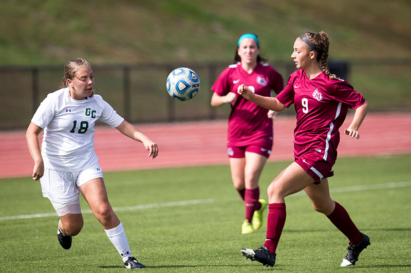 Two Meredith College soccer student-athletes going after the ball in a game.