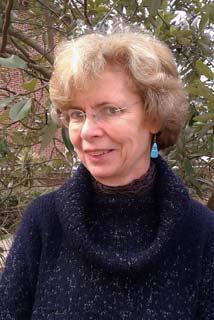 Veronique Machelidon in Blue coat wearing spectacles