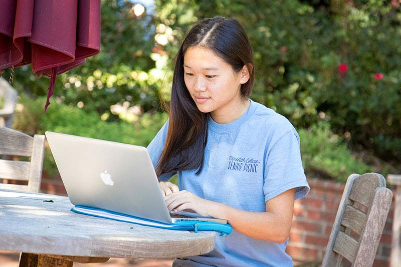 Woman wearing blue shirt looking at an open laptop