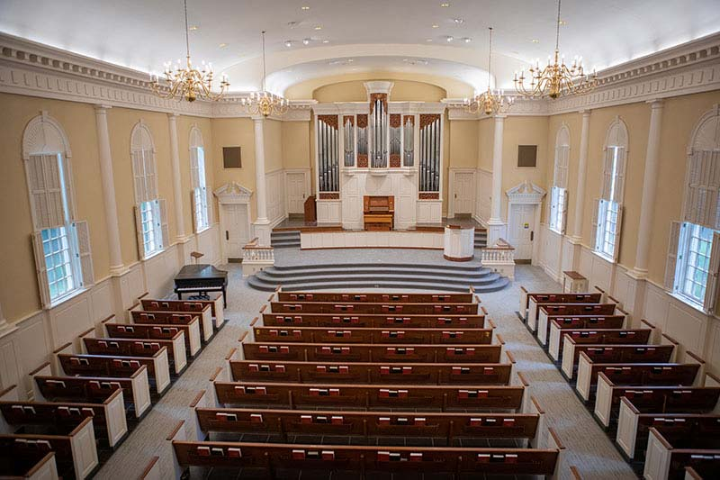 Image of the inside of the Meredith Chapel. Shows tan walls with multiple rows of pews and stairs leading to the alter and a large organ behind that.