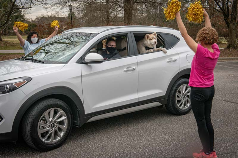 Education Faculty with Pom Pom welcoming new student in car