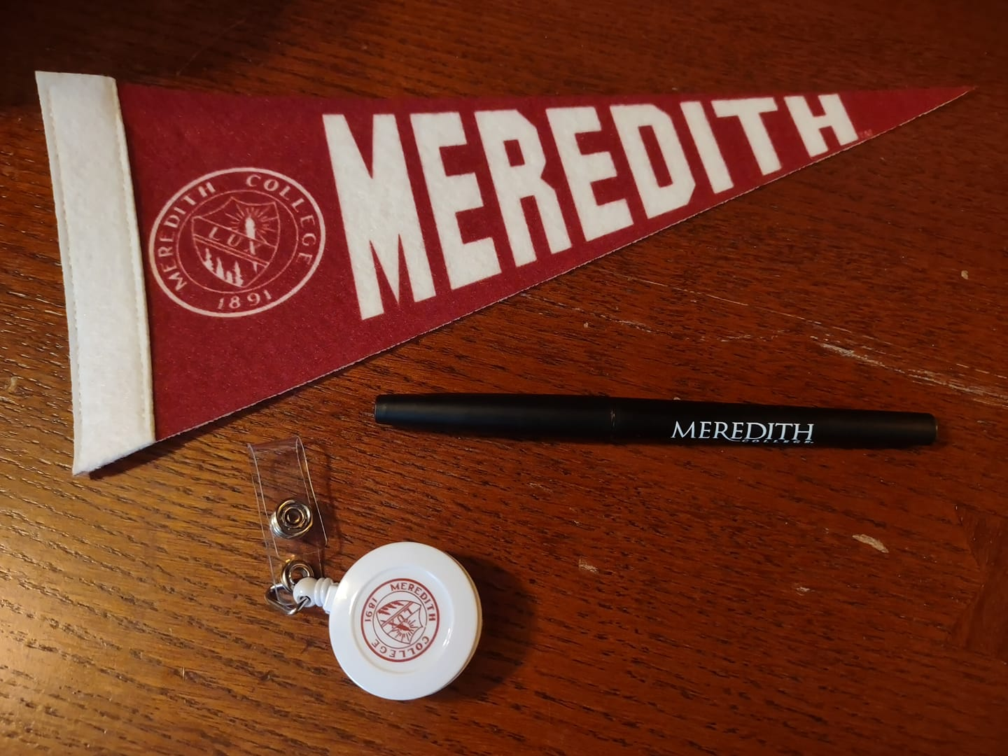 Teacher gifts including pennant, pen, and badge holder